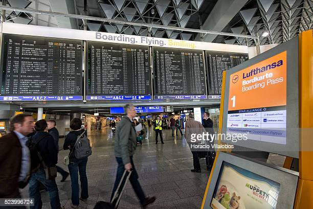 Travelers walk by the departures billboard announcing cancellations in Terminal 1 on the first day of Lufthansa pilots' strike at Frankfurt...