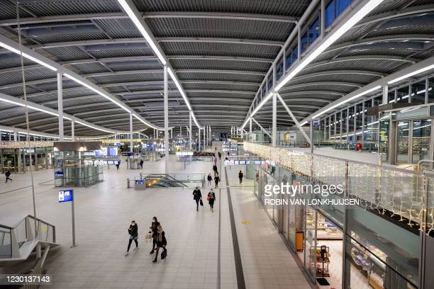 Travelers walk in Utrecht Central Station, on December 15 on the first day of a lockdown decided by the government to stop the spread of the Covid-19...