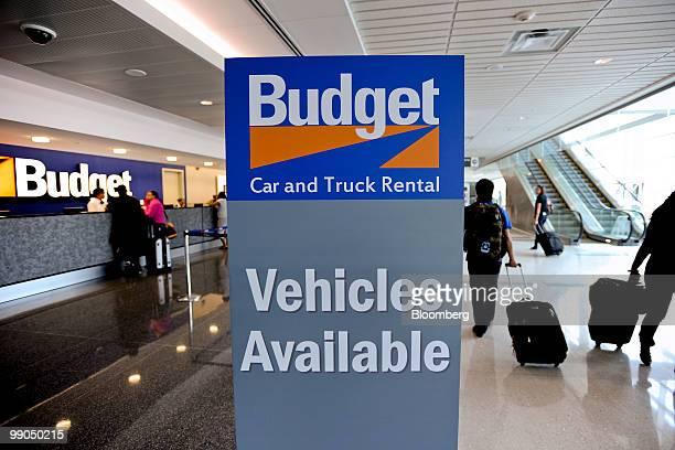 Travelers walk past a Budget sign at HartsfieldJackson Atlanta International Airport in Atlanta Georgia US on Friday May 7 2010 Avis Budget Group Inc...