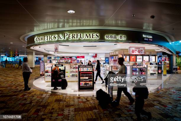 Travelers walk past a Hotel Shilla Co Shilla Duty Free store at Terminal 1 of Changi Airport in Singapore on Thursday Dec 13 2018...