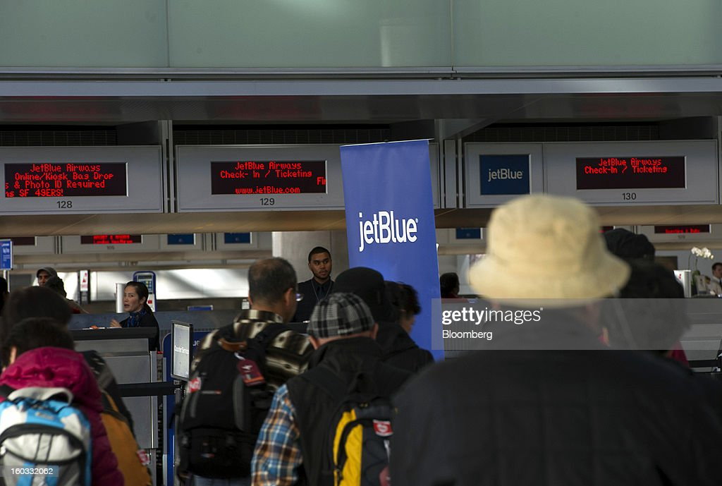 Travelers walk past a JetBlue Airways Corp. check-in counter at San Francisco International Airport in San Francisco, California, U.S., on Monday, Jan. 28, 2013. JetBlue Airways Corp. fell the most in about two months after fourth-quarter profit tumbled 96 percent, more than analysts projected, as superstorm Sandy forced flight cancellations and reduced travel demand. Photographer: David Paul Morris/Bloomberg via Getty Images
