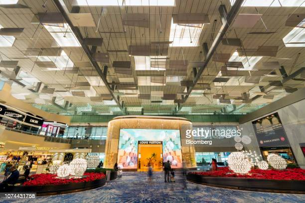 Travelers walk past a LVMH Moet Hennessy Louis Vuitton SE store at Terminal 3 of Changi Airport in Singapore, on Thursday, Dec. 13, 2018....