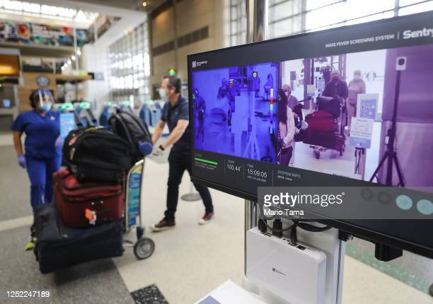 Travelers walk past a test system of thermal imaging cameras which check body temperatures at Los Angeles International Airport amid the COVID19...
