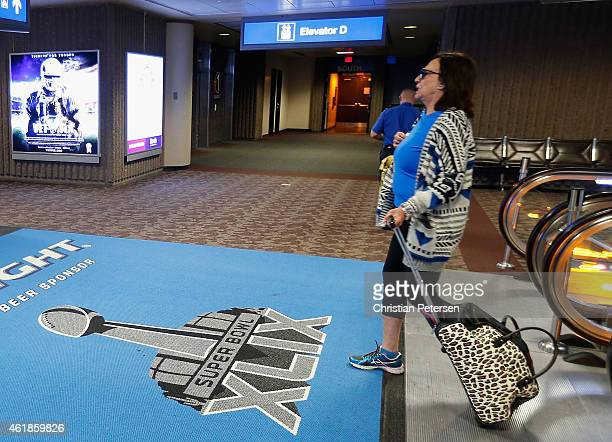 Travelers walk past Super Bowl XLIX logos at Phoenix Sky Harbor International Airport on January 19 2015 in Phoenix Arizona The NFL Super Bowl XLIX...
