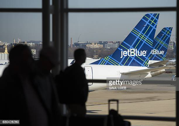 Travelers walk past the tails of JetBlue airplanes in the airport terminal at Ronald Reagan Washington National Airport in Arlington Virginia...