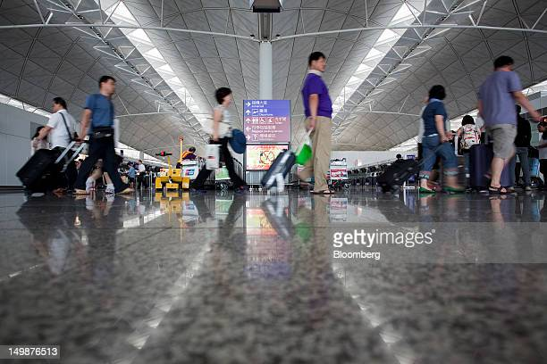 Travelers walk through the departure hall of Chek Lap Kok Airport in Hong Kong China on Sunday Aug 5 2012 The number of overseas visitors to Hong...