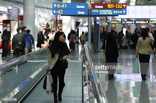Travelers walk through the duty free shopping area at Incheon International Airport in Incheon South Korea on Tuesday Jan 10 2012 Incheon...