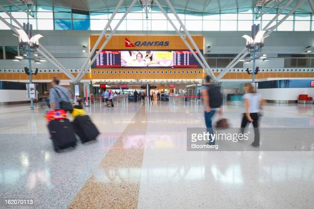 Travelers walk through the Qantas Airways Ltd domestic terminal at Sydney Airport in Sydney Australia on Tuesday Feb 19 2013 Qantas Airways is...