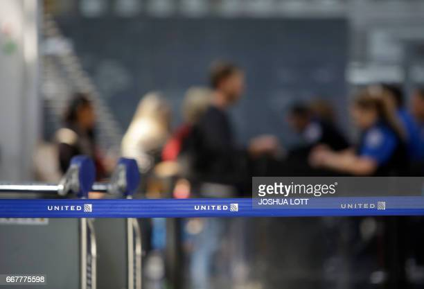 Travelers walk through the United Airlines terminal at O'Hare International Airport on April 12 2017 in Chicago Illinois United Airlines has been...