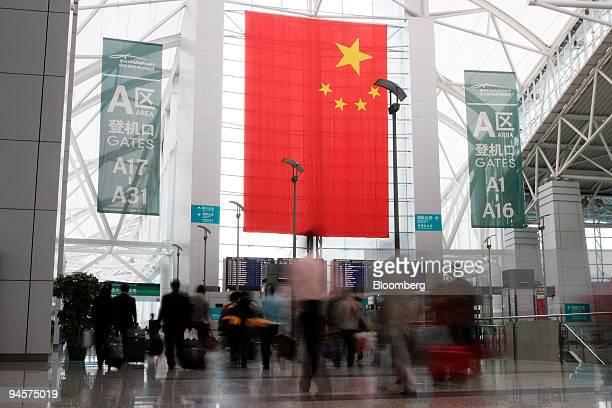 Travelers walk to the departure area at the Guangzhou Baiyun International Airport in Guangzhou China on Monday March 26 2007 Guangzhou Baiyun...
