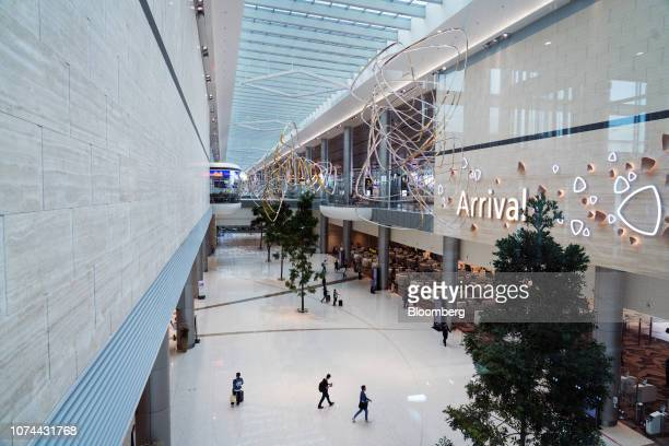 Travelers walk towards immigration clearance counters stand in the arrival hall at Terminal 4 of Changi Airport in Singapore on Thursday Dec 13 2018...