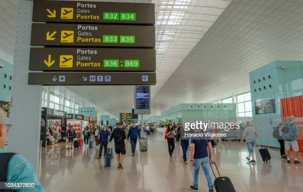 Travelers walk under airport information signs in Terminal 1 of Barcelona El Prat Airport on September 09 2018 in Barcelona Spain Barcelona El Prat...