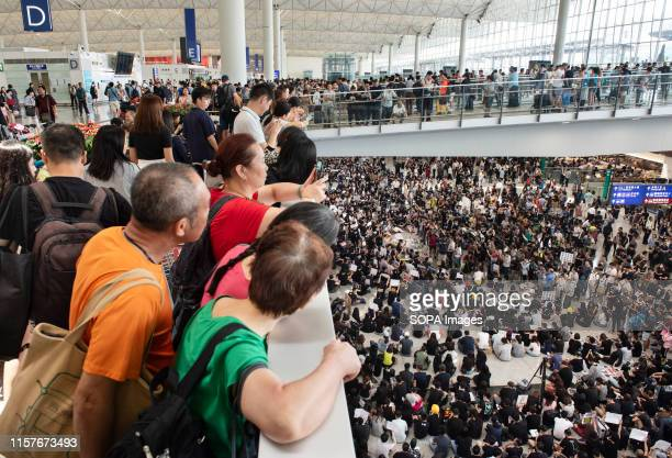 Travelers watch hundreds of anti government protesters staged a sit in protest at the Hong Kong international airport terminal the first of three...