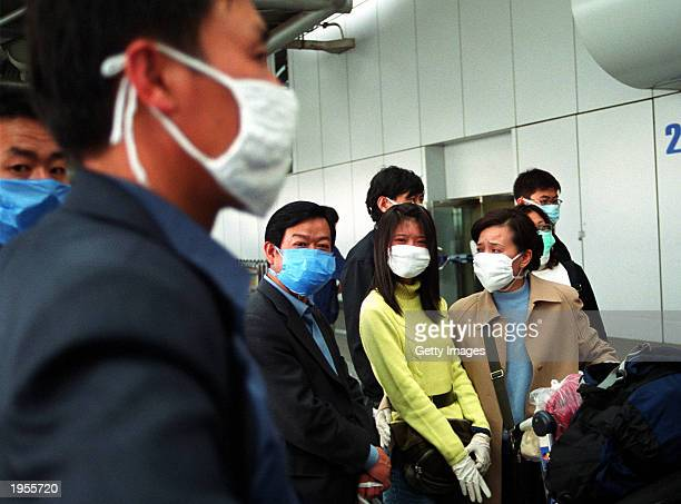 Travelers wear face masks as they arrive at Beijing's Capital Airport April 28 2003 in Beijing China To combat the spread of the Severe Acute...