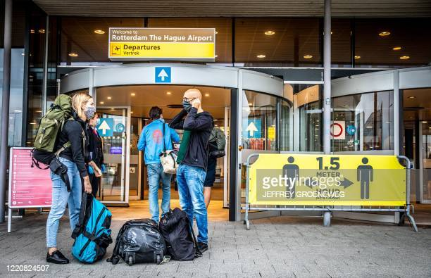 Travelers wear face masks as they arrive to take a flight, the first one since the coronavirus COVID-19 outbreak, at Rotterdam The Hague Airport in...