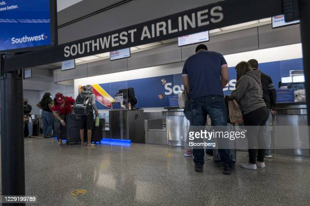 Travelers wear protective masks at a Southwest Airlines Co. Check-in area at Oakland International Airport in Oakland, California, U.S., on Monday,...