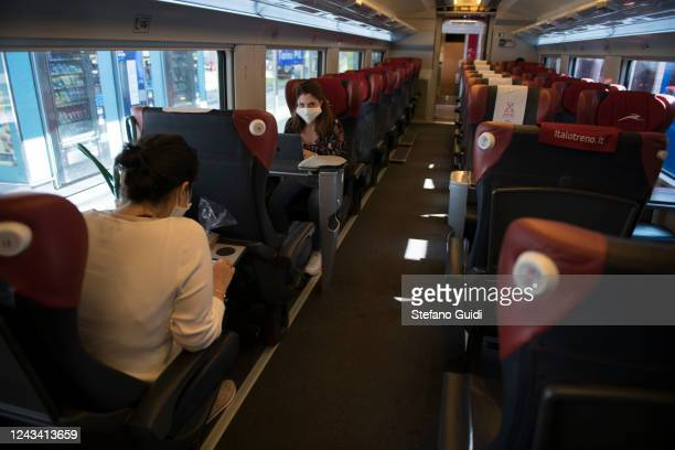 Travelers wearing a protective mask sit inside a Italo Train before departing at the Porta Nuova railway station on June 03 2020 in Turin Italy Today...