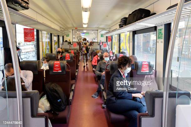 Travelers wearing a protective masks sit inside a Train before departing at the Trento railway station on June 04 2020 in Trento Italy Many Italian...