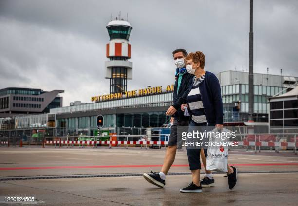Travelers wearing face masks arrive to take a flight, the first one since the coronavirus outbreak, at Rotterdam The Hague Airport in Rotterdam, the...