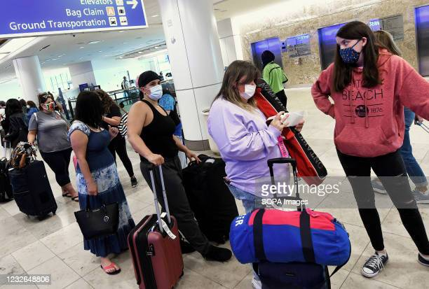 Travelers wearing face masks as a preventive measure against the spread of covid-19 wait in line at the Southwest Airlines ticket counter at Orlando...