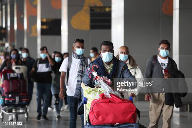 Travelers wearing face masks can be seen as they pass through Indira Gandhi International Airport on March 11 2020 in New Delhi India India has...
