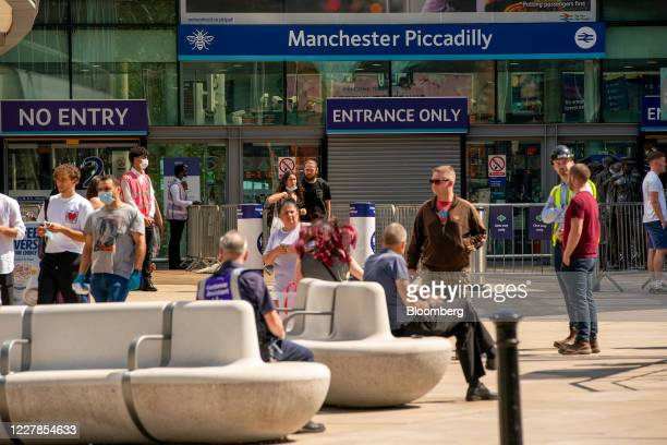 Travelers wearing protective face masks arrive at Manchester Piccadilly railway station, Manchester, U.K., on Friday, July 31, 2020. More than 4...