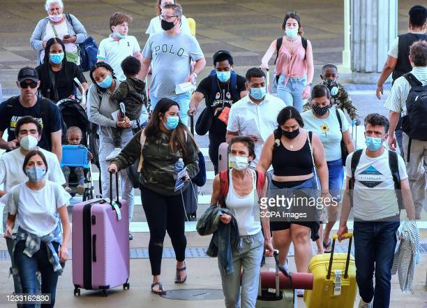 Travelers wearing protective face masks arrive at Orlando International Airport on the Friday before Memorial Day. As more and more people have...