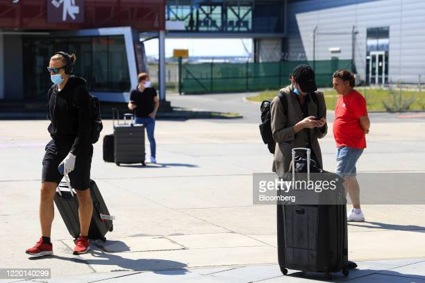 Travelers wearing protective face masks stand with their luggage after arriving on a flight from London, U.K. As European Union travel restrictions...