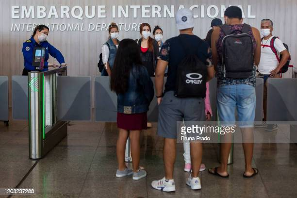 Travelers wearing protective face masks wait at the departures gate of Tom Jobim International Airport on March 25 2020 in Rio de Janeiro Brazil The...