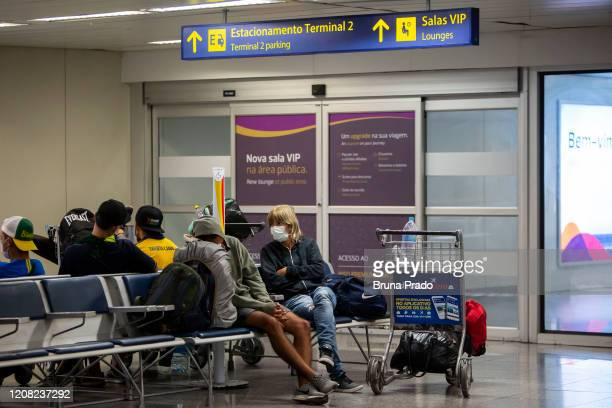 Travelers wearing protective face masks wait at the Tom Jobim International Airport on March 25 2020 in Rio de Janeiro Brazil The federal government...