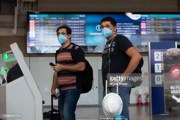 Travelers wearing protective face masks wait with their luggage at Tom Jobim International Airport on March 25 2020 in Rio de Janeiro Brazil The...