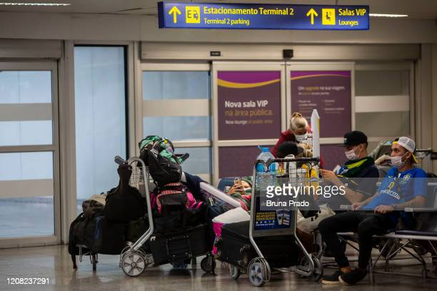 Travelers wearing protective face masks wait with their luggage at the Tom Jobim International Airport on March 25 2020 in Rio de Janeiro Brazil The...