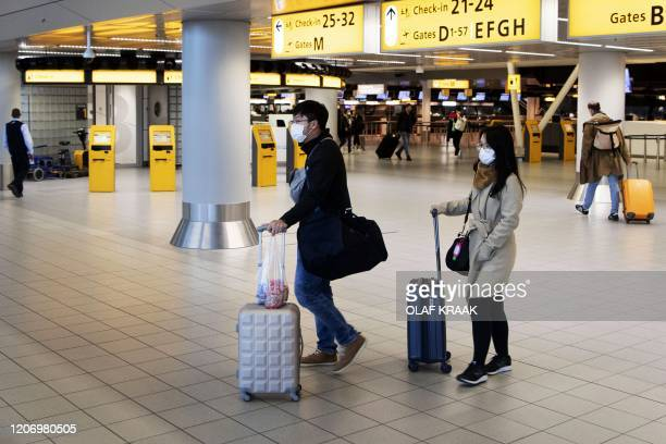 Travelers wearing protective face masks walk at Schiphol Airport in Amsterdam on March 13 amid an outbreak of COVID19 the new coronavirus The...