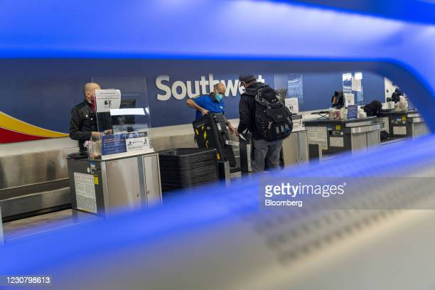 Travelers wearing protective masks check-in at the Southwest Airlines counter at Oakland International Airport in Oakland, California, U.S., on...
