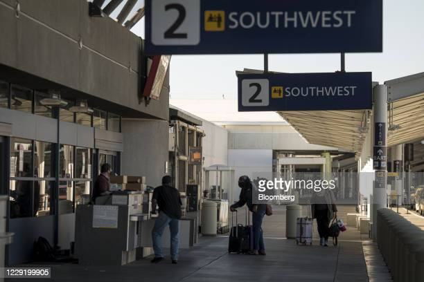 Travelers wearing protective masks pull luggage outside a Southwest Airlines Co. Check-in area at Oakland International Airport in Oakland,...