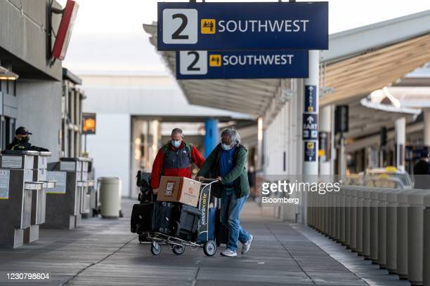 Travelers wearing protective masks push luggage outside the Southwest Airlines check-in area at Oakland International Airport in Oakland, California,...