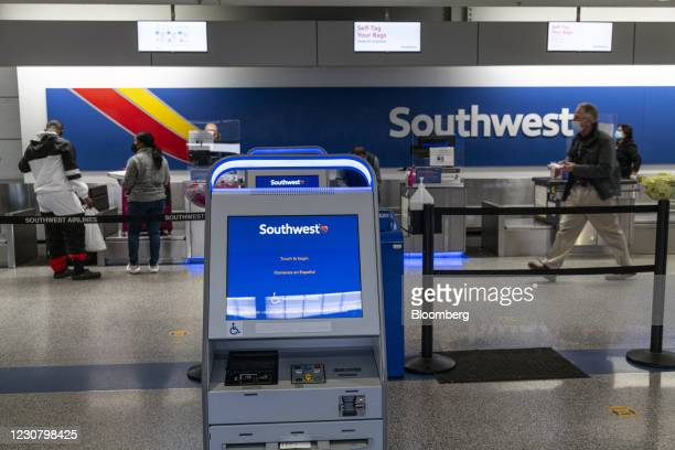 Travelers wearing protective masks speak with an attendant at the Southwest Airlines check-in area at Oakland International Airport in Oakland,...
