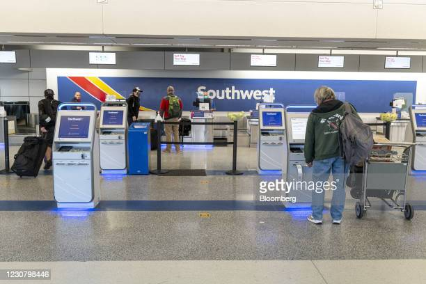 Travelers wearing protective masks use automated check-in kiosks at the Southwest Airlines check-in area at Oakland International Airport in Oakland,...