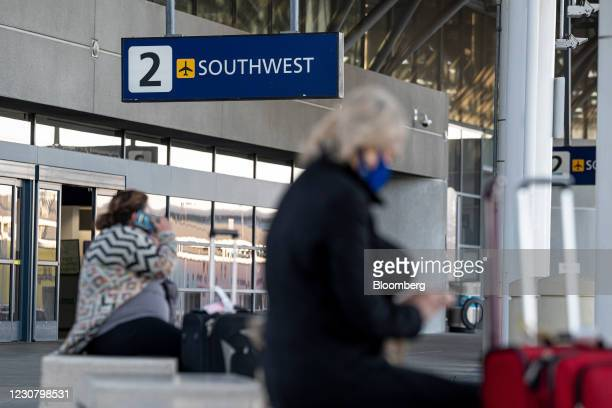 Travelers wearing protective masks wait for transportation outside the Southwest Airlines Co. Terminal at Oakland International Airport in Oakland,...