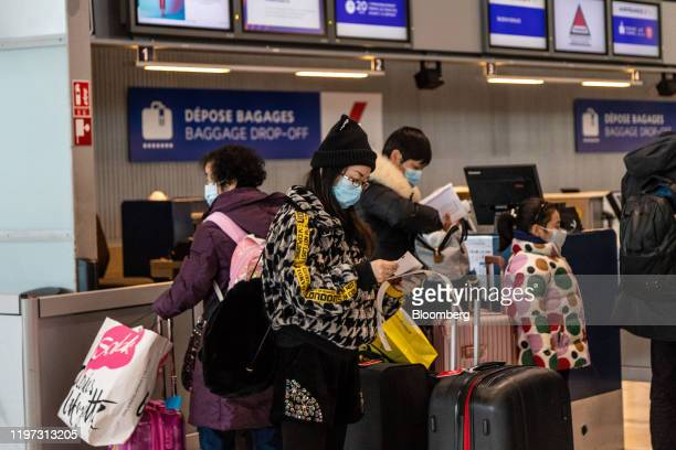 Travelers wearing protective masks wait in the baggage dropoff area at Charles de Gaulle airport operated by Aeroports de Paris in Roissy France on...