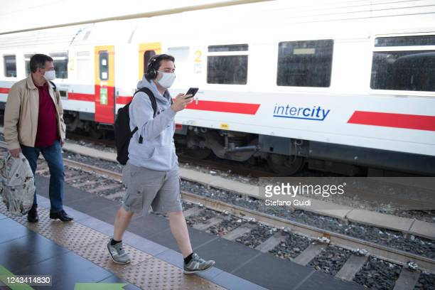 Travelers wearing protective masks walk a platform after getting off an interregional train at the Porta Nuova railway station on June 03 2020 in...