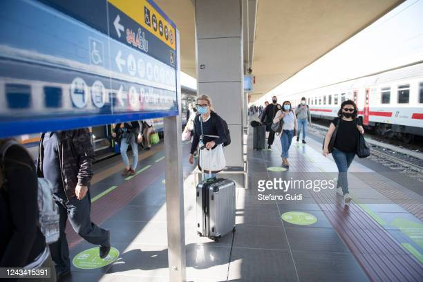 Travelers wearing protective masks walk the platform after getting off an interregional train at the Porta Nuova railway station on June 03 2020 in...