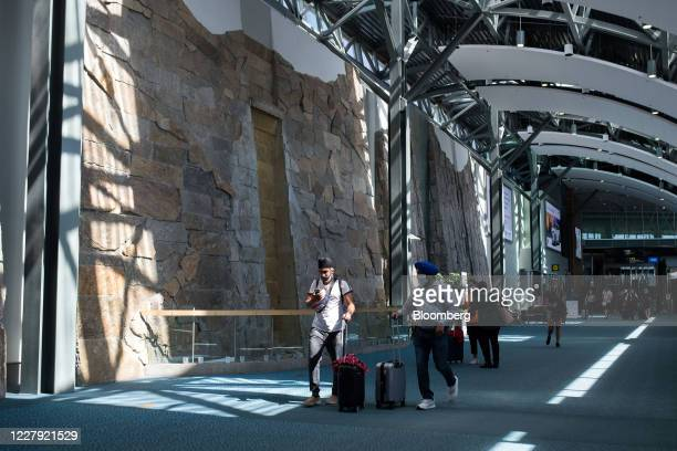 Travelers wearing protective masks walks through Vancouver International Airport in Vancouver, British Columbia, Canada, on Tuesday, Aug. 4, 2020....