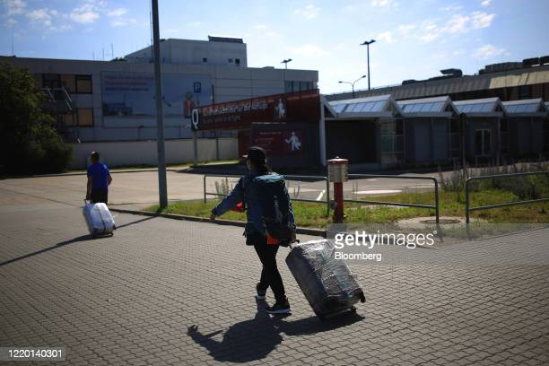 Travelers wheel their luggage after arriving on a flight from London, U.K. As European Union travel restrictions are lifted at Berlin Shoenfeld...