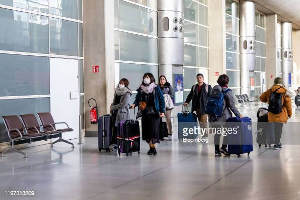 Travelers wheel their luggage while wearing protective face masks at Charles de Gaulle airport operated by Aeroports de Paris in Roissy France on...