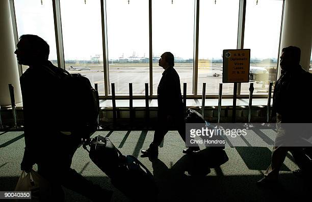 Travelers with bags walk toward the passport control line upon arriving to Newark International Airport August 24 2009 in Newark New Jersey Officials...