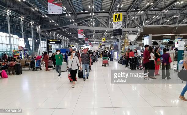 travelers with luggage at the airport in bangkok wearing masks for protection against the coronavirus - thailand stock pictures, royalty-free photos & images