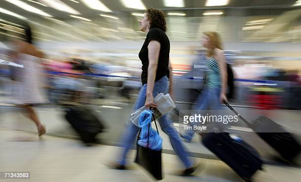 Travelers with wheeled luggage hustle through Terminal 3 June 30, 2006 at O'Hare International Airport in Chicago, Illinois. Heavy holiday travel is...
