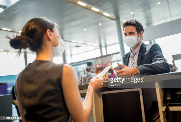 traveling business man doing the check-in at the airport wearing a facemask - biosecurity stock pictures, royalty-free photos & images