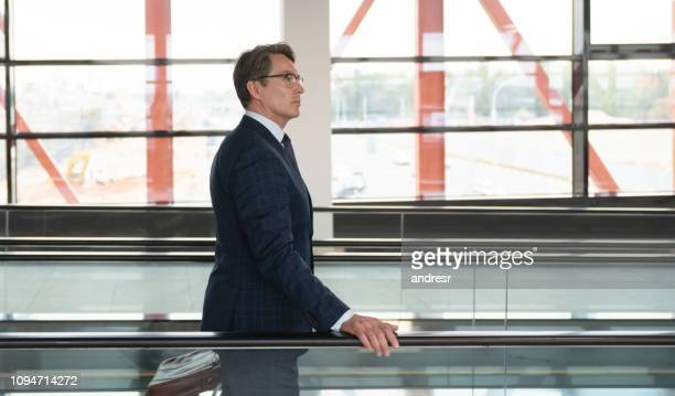 Traveling business man on a moving walkway at the airport